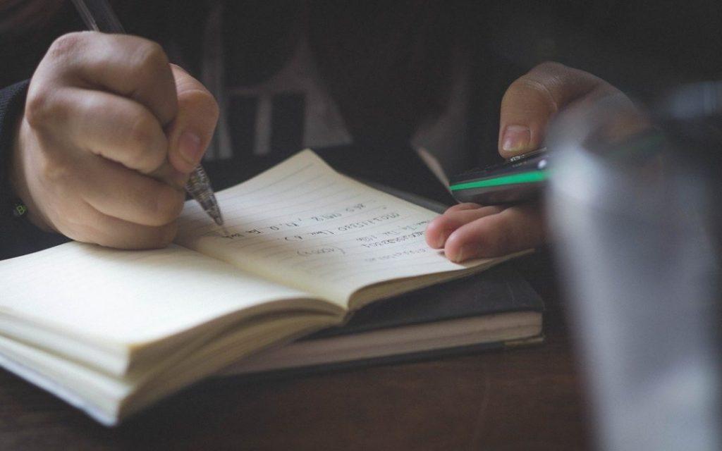 student writing in notebook mathematics