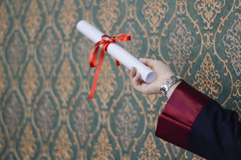 A graduate holding a diploma